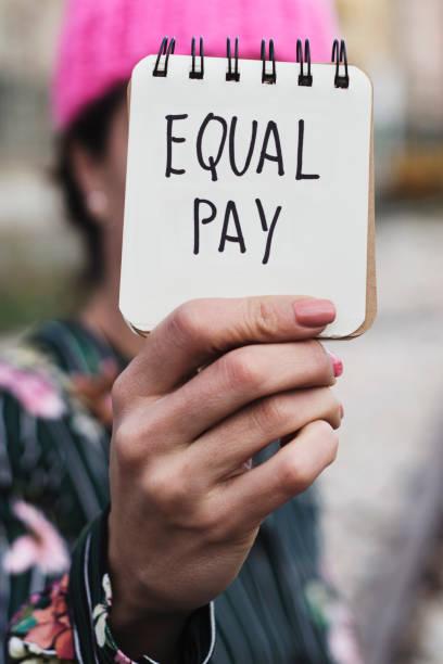 Frau mit einem rosa Hut und den Text Lohngleichheit – Foto
