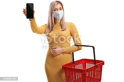Woman with a protective face mask holding an empty shopping basket and showing a mobile phone isolated on white background