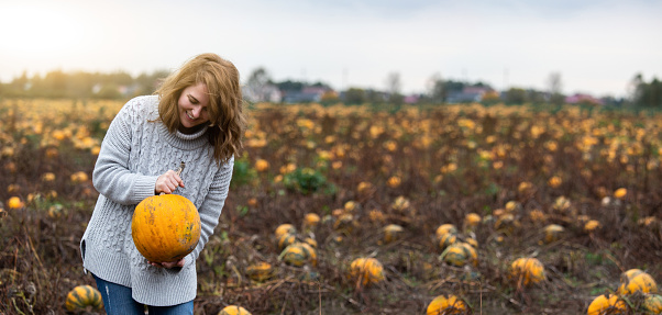 Woman with a pumpkin on a pumpkin field