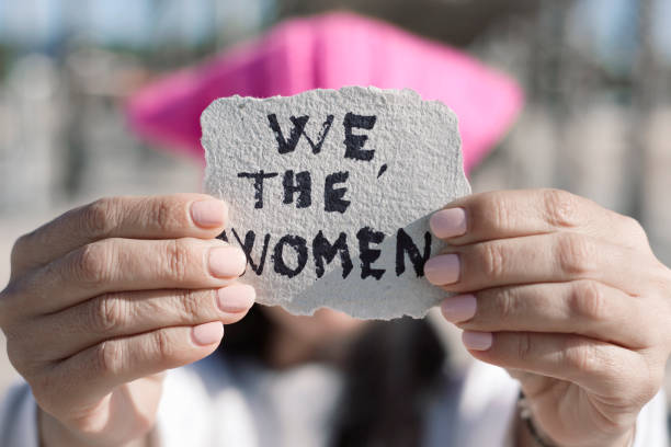 woman with a pussyhat and the text we the women stock photo
