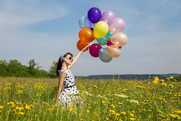 frau mit einem rockabilly kleid mit punkten und viele ballons - rock n roll kleider stock-fotos und bilder