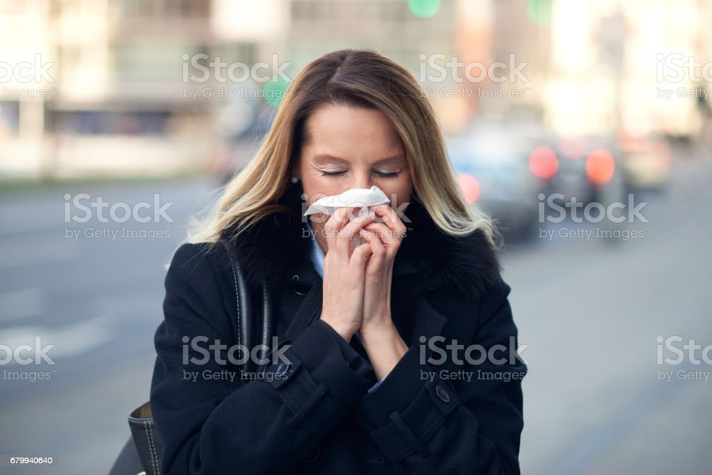Woman with a seasonal winter cold blowing her nose stock photo