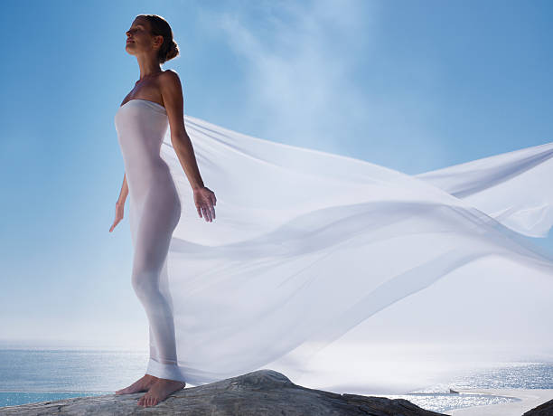 Woman with a sheer sheet with ocean backdrop stock photo