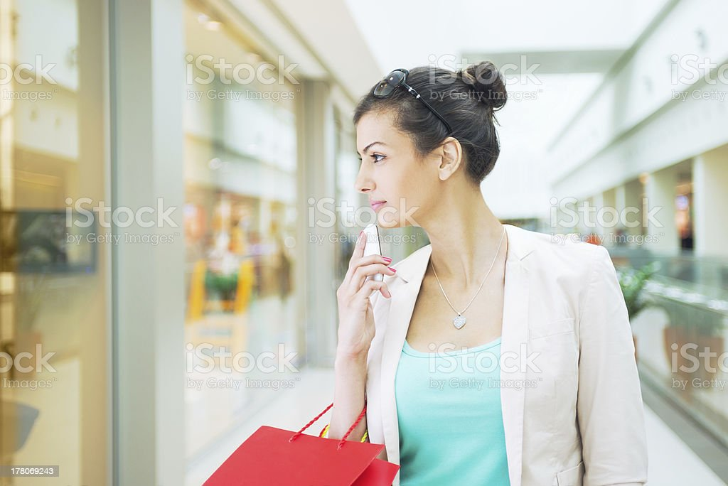 Woman with a shopping bag is interested in a window display stock photo