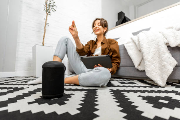 Woman with a smart speaker and tablet at home stock photo