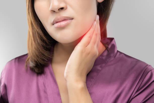mulher com dor de garganta, segurando seu pescoço, cinza fundo, linfadenopatia, pessoas com o conceito de problema de saúde. - cancer da tireoide - fotografias e filmes do acervo