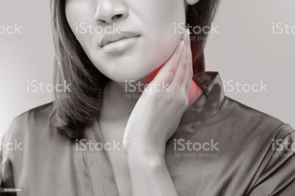 Woman with a sore throat holding her neck, On gray Background, Lymphadenopathy, People with health problem concept. stock photo