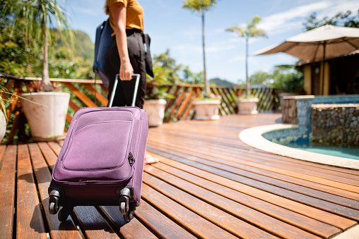 Young woman pulling a wheeled suitcase arriving at a tourist resort in the tropics