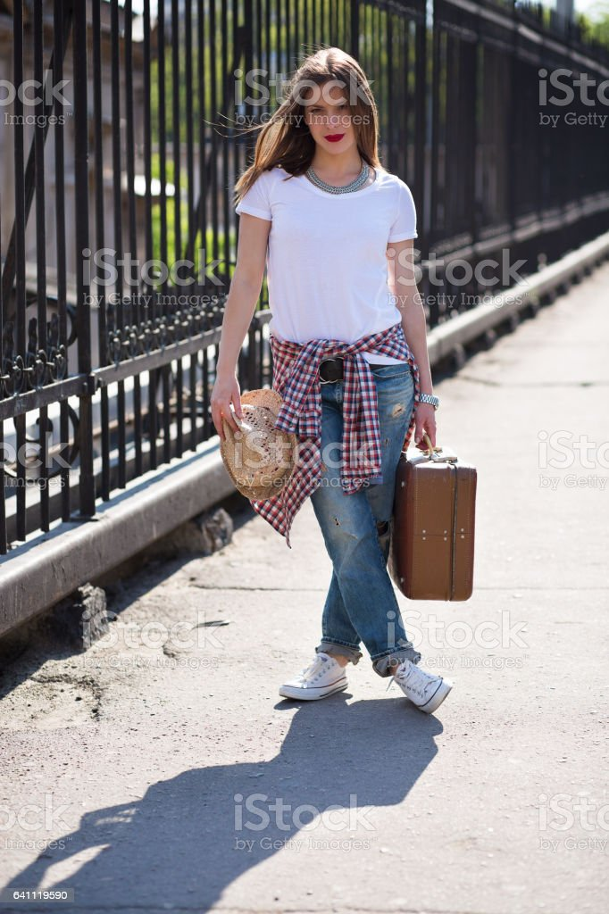 Woman with a suitcase in the city stock photo