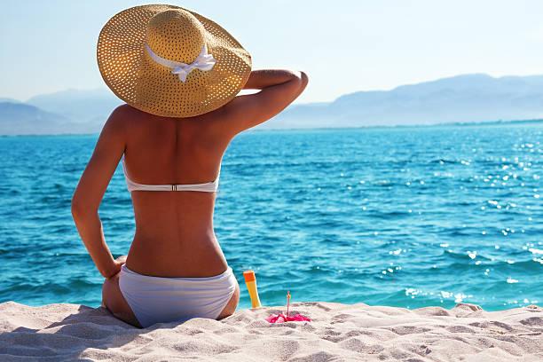 a woman with a sun hat is sitting on the beach - gebruind stockfoto's en -beelden