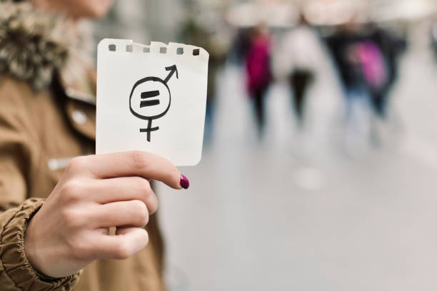 woman with a symbol for gender equality closeup of a young caucasian woman in the street showing a piece of paper with a symbol for gender equality drawn in it human rights stock pictures, royalty-free photos & images