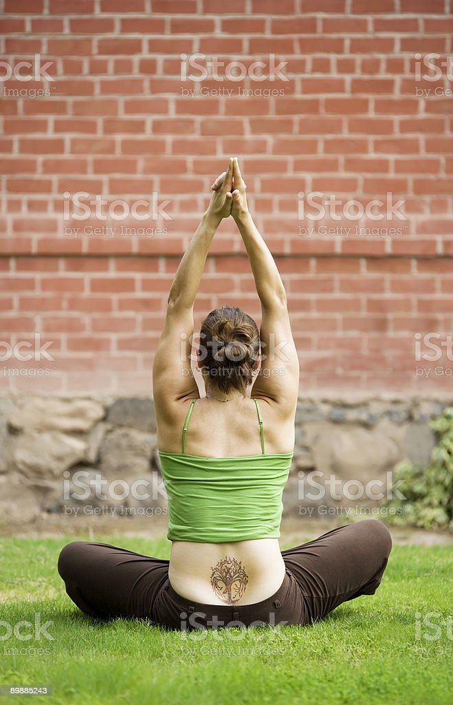 Woman with a Tattoo on Her Back Doing Yoga royalty free stockfoto