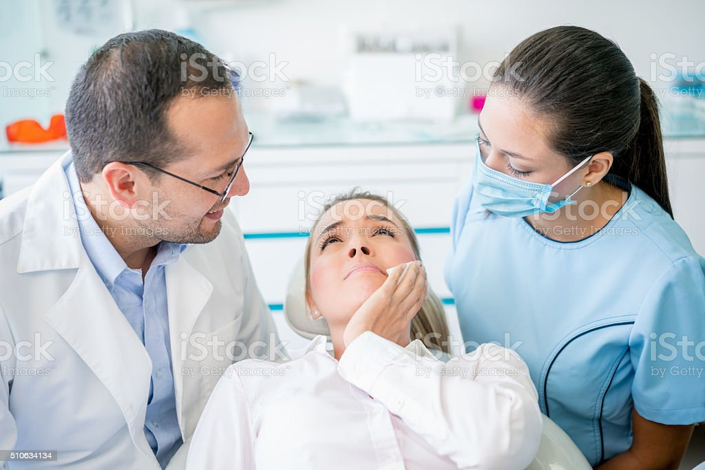 Woman with a tooth pain at the dentist stock photo