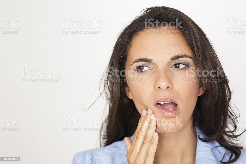 A woman with a toothache touching her mouth on white stock photo