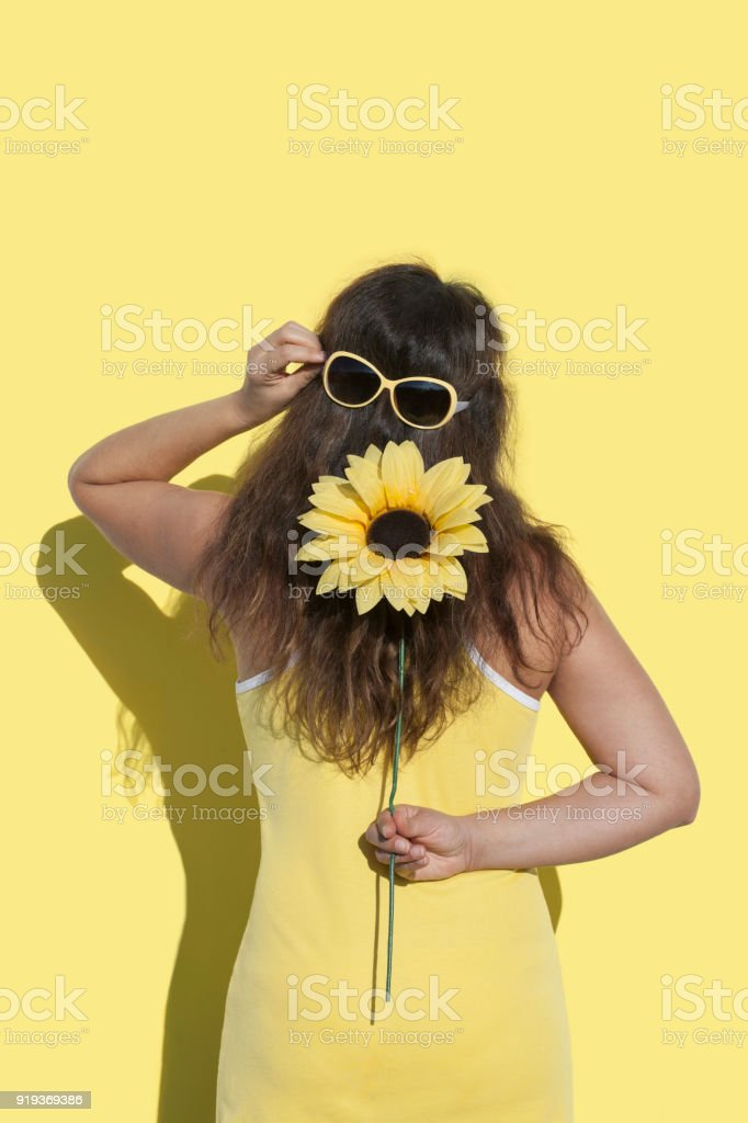 Woman with a yellow flower and sunglasses stock photo