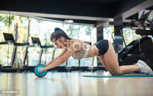 istock Woman with ab wheel 876598310