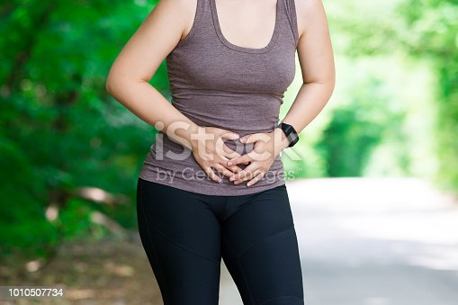 istock Woman with abdominal pain, injury while running, trauma during workout 1010507734