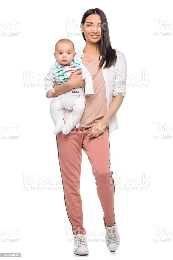 woman with adorable baby in hand looking at camera stock photo