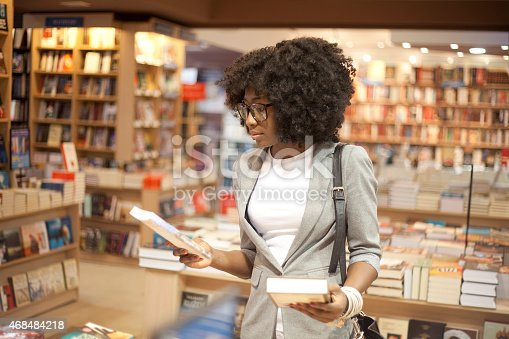 istock Woman with afro hair choosing books in a bookstore 468484218