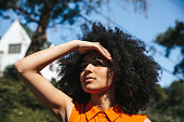 istock Woman with afro hair covering her eyes from the sun 1296154653
