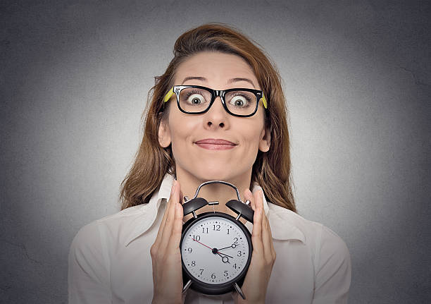 woman with alam clock alarm clock. headshot young excited funny looking business woman holding alarm clock isolated grey wall background. Human face expressions, emotions. Time, punctuality, busy schedule concept fresh start morning stock pictures, royalty-free photos & images