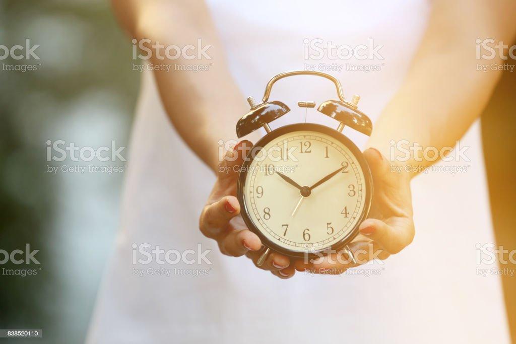 Woman with alarm clock stock photo