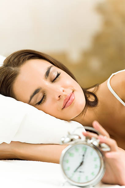 Woman with alarmclock lying on bed, at home stock photo