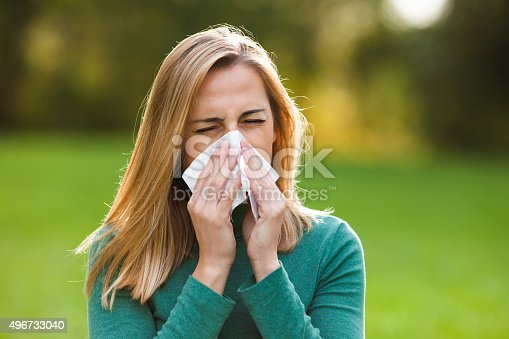 istock Woman with allergy symptom blowing nose 496733040