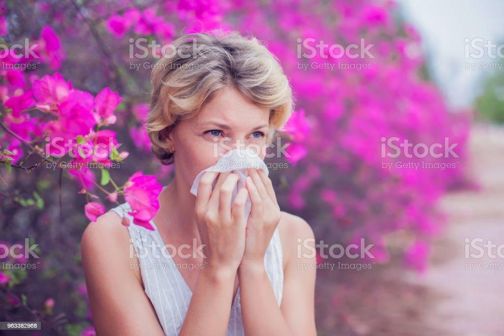 Woman with allergy symptom blowing nose - Zbiór zdjęć royalty-free (Alergia)