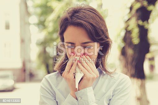 istock Woman with allergy symptoms blowing nose 824613300