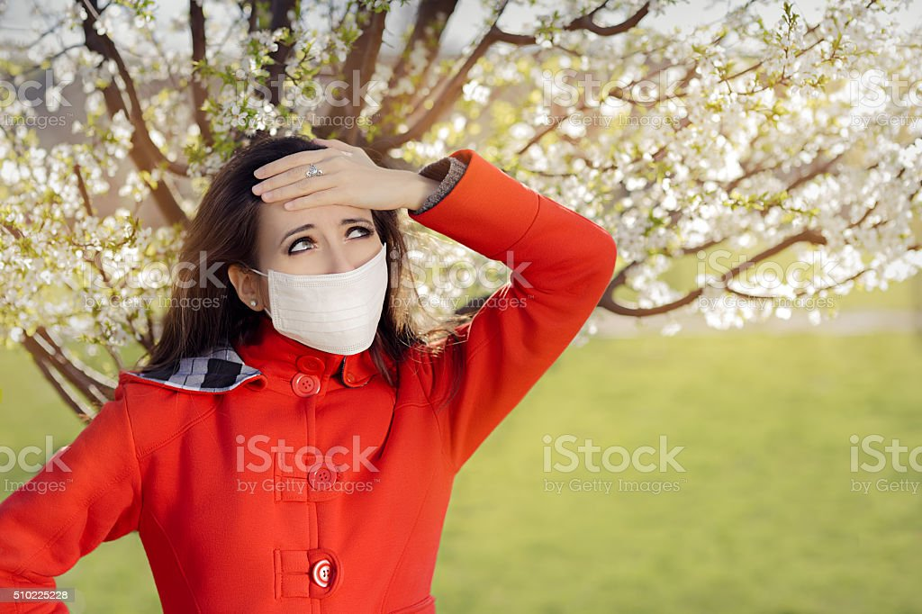 Woman with Allergy with Respirator Mask in Spring Blooming Decor stock photo