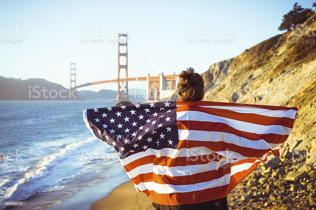 Woman with American Flag and Golden Gate Bridge, San Francisco stock photo