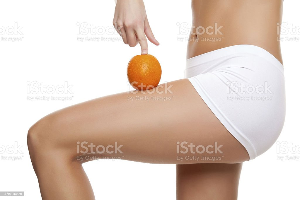 Woman with an orange showing a perfect skin stock photo