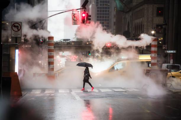 en kvinna med ett paraply och röda högklackade skor passerar den 42nd street på manhattan. - kvinna ventilationssystem bildbanksfoton och bilder