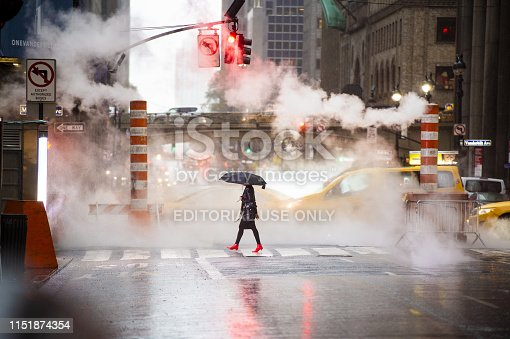 Manhattan, New York City, United States of America, October 29, 2017. A woman with an umbrella and red high heels shoes is crossing the 42nd street in Manhattan. Cars and steam coming out from from the manholes in the background. New York City, Usa.