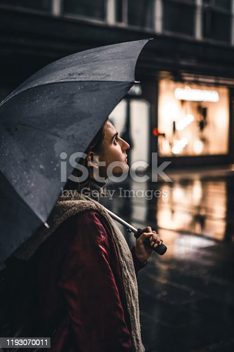 Young Beautiful Female Tourist with Backpack is Walking with Umbrella in the Street and Exploring the City During a Wet Rainy Day.