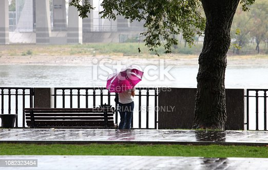 Rostov-on-Don, Russia - September 16, 2018: Woman with an umbrella stands on the bank of the Don River in the rain.