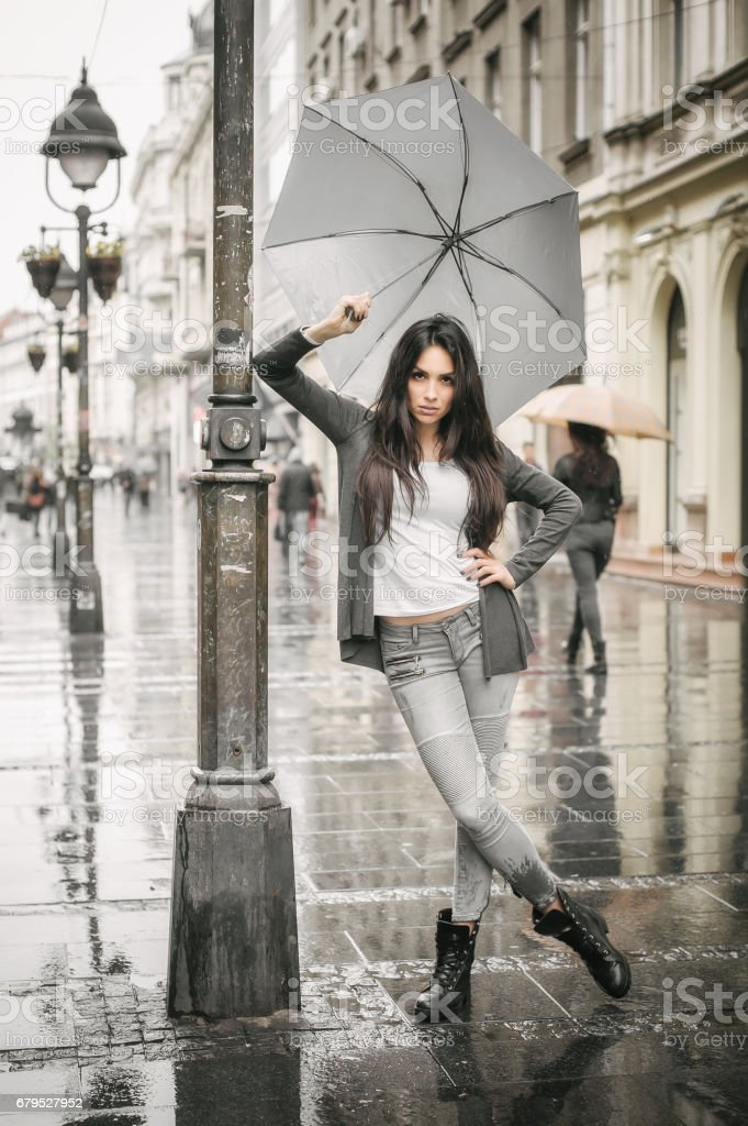 Woman with an umbrella under rain on a city street royalty-free stock photo