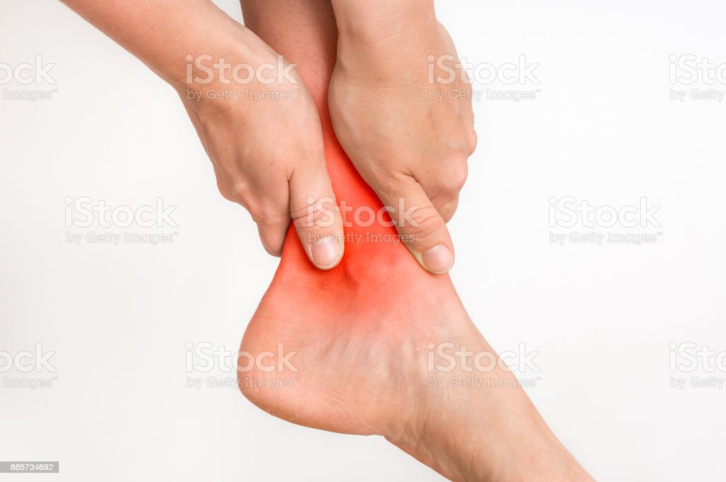 Woman with ankle pain holding her aching leg stock photo