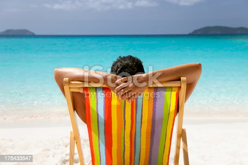 istock woman with arms behind her head sunbathing at tropical beach 175433547