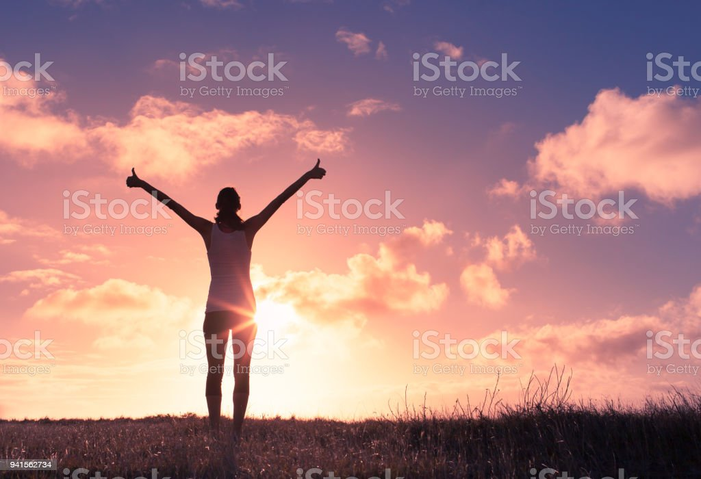 Woman with arms in the air giving thumbs up. stock photo