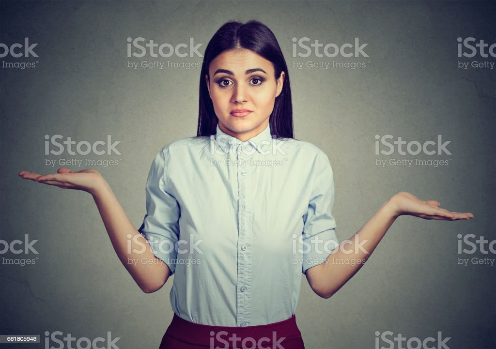Woman with arms out shrugs shoulders stock photo
