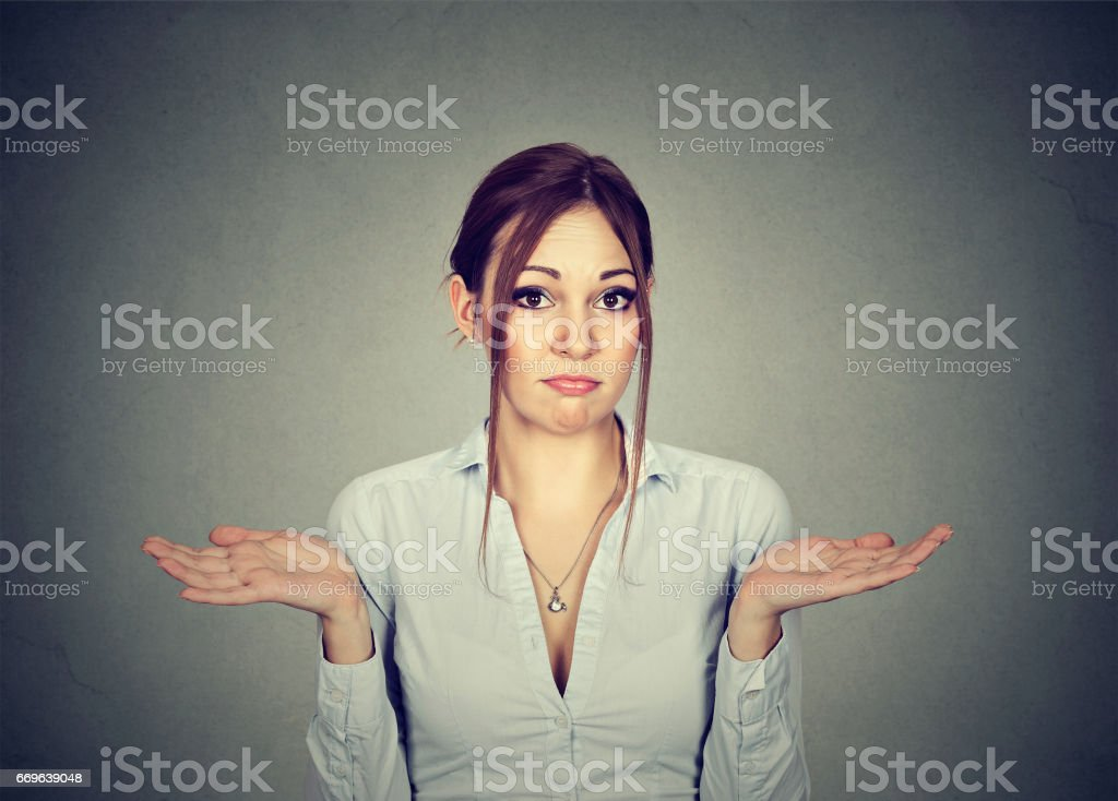 Woman with arms out shrugs shoulders so what I don't know stock photo