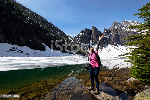 Woman with arms outstretched enjoys beautiful A woman enjoys taking taking pictures at historic Lake Agnes Tea House in Banff National Park Rocky Mountains of Alberta Canada