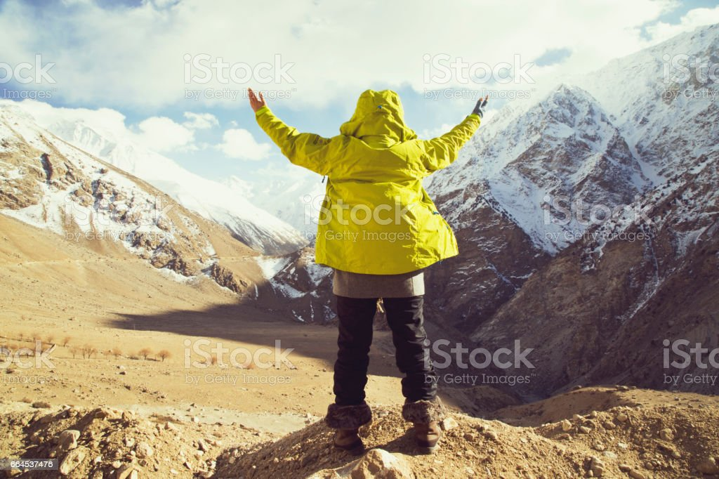 Woman with arms outstretched in front of snowcapped Himalayan mountain royalty-free stock photo
