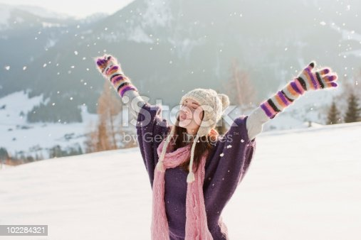 istock Woman with arms outstretched in snow 102284321