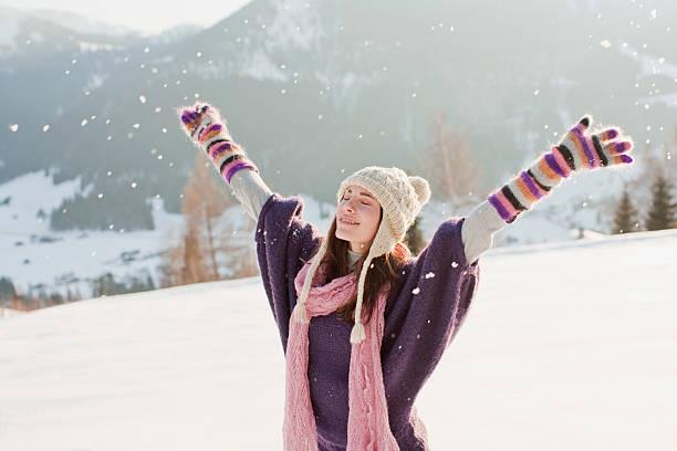 frau mit ausgestreckten armen im schnee - kalte sonne stock-fotos und bilder