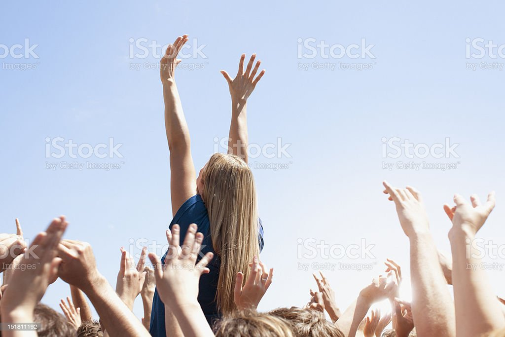 Woman with arms raised above crowd stock photo