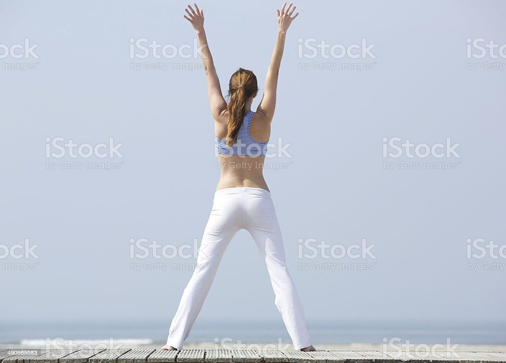 Woman with arms raised at the beach royalty-free stock photo