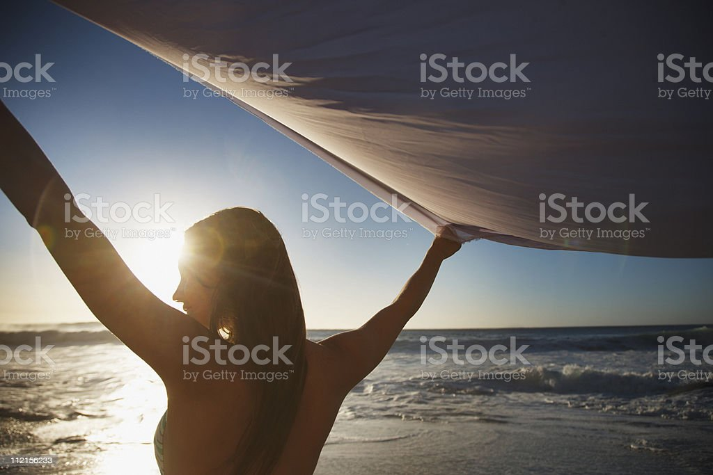 Woman with arms raised holding fabric on beach stock photo
